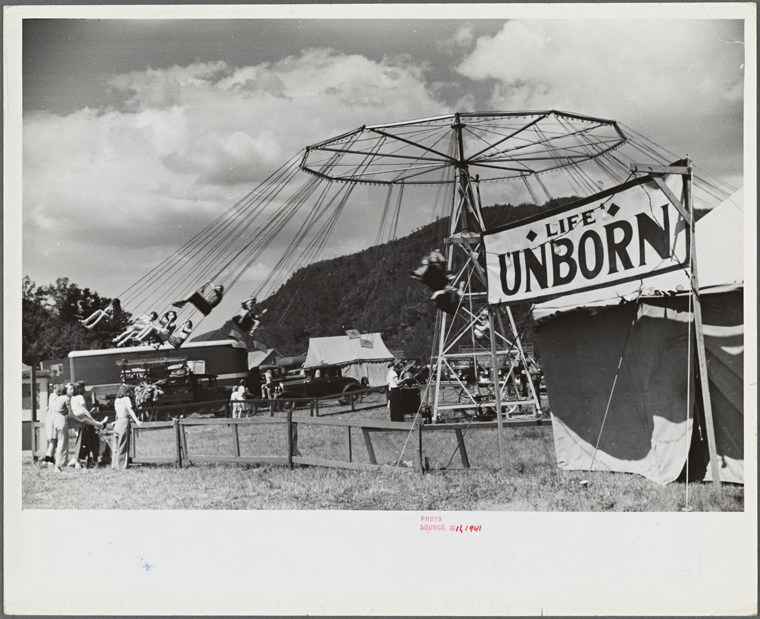 "A ride at a fair with a tent saying ""Life's Unborn"""
